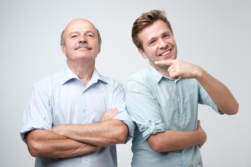 Handsome mature son is proud of his senior father. stock image