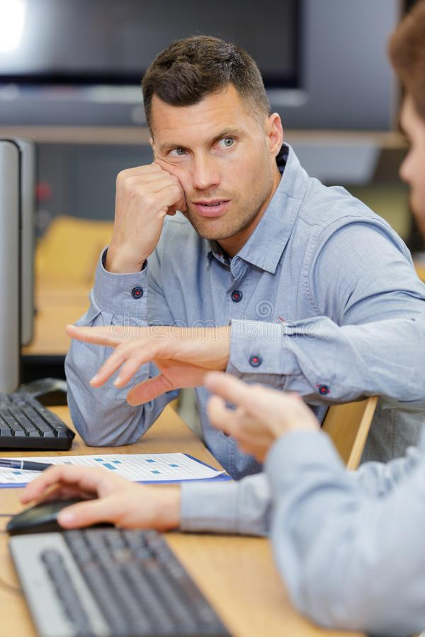 Handsome mature student listening to colleague royalty free stock photos
