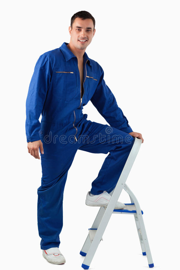 A Handsome Mechanic Climbing On A Stool Stock Photo