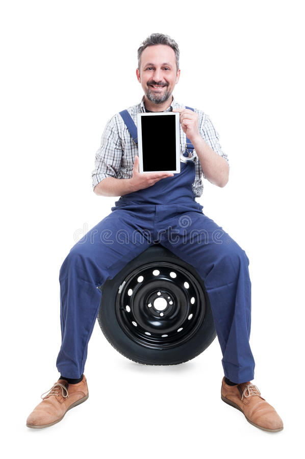 Handsome mechanic sitting on tire and showing tablet royalty free stock photo
