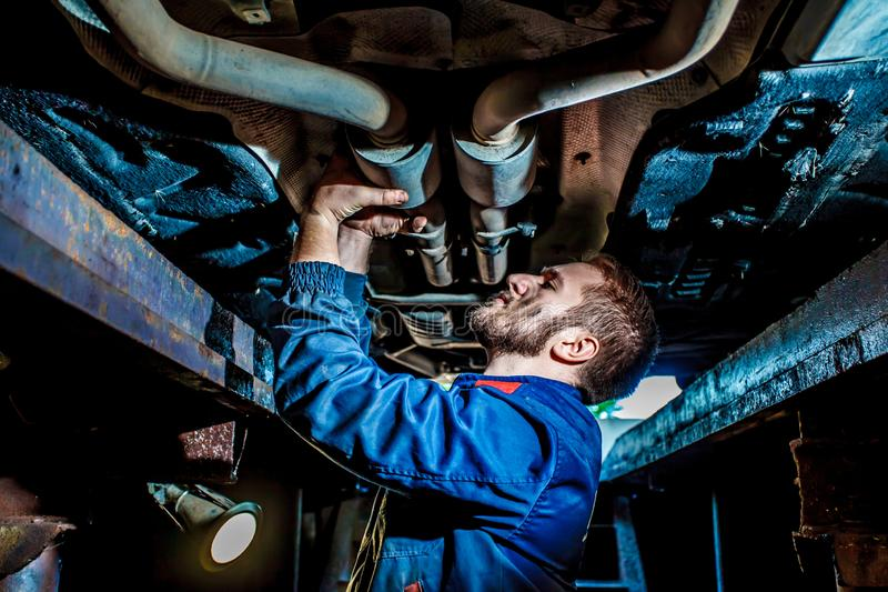 Handsome mechanic in uniform are working in auto service with lifted vehicle. Car repair and maintenance. royalty free stock photos