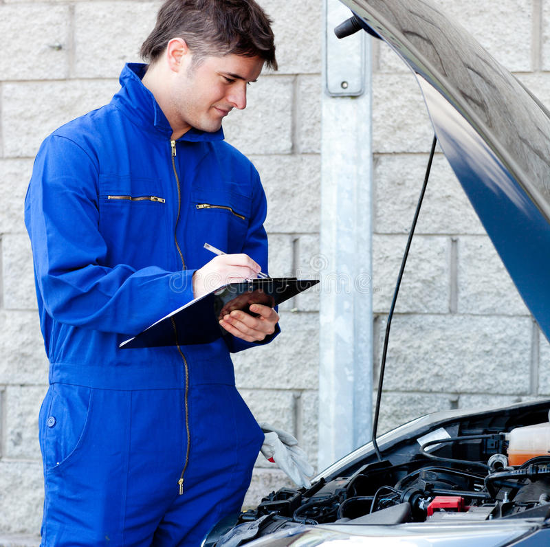 Handsome mechanic writing on a clipboard royalty free stock photo