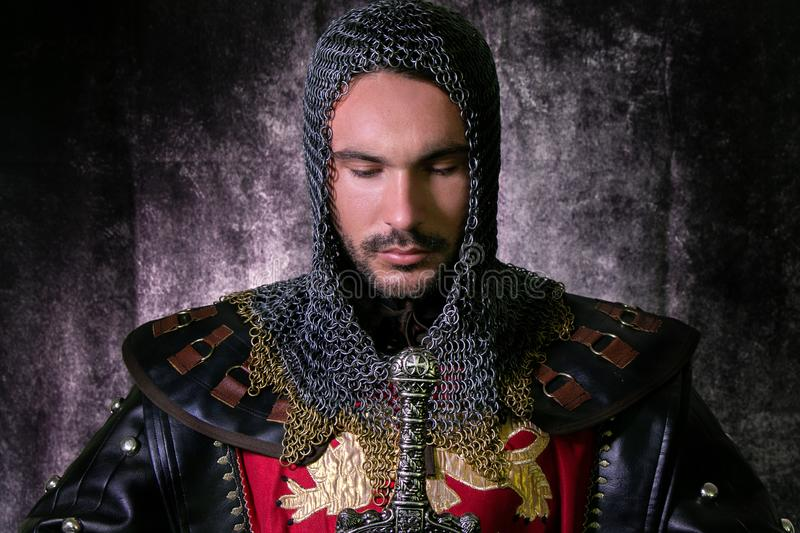 Portrait of handsome medieval knight in suit of armour with beard looking down in contemplation. Handsome medieval knight in suit of armour with beard and sword royalty free stock photo