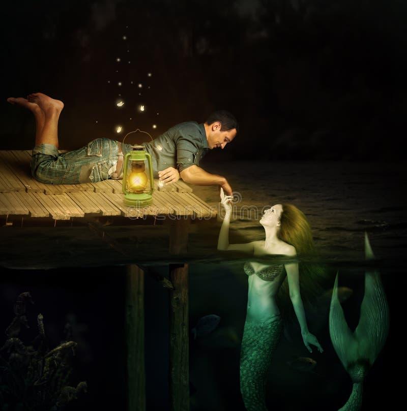 Handsome men and beautiful mermaid. Love between handsome men and beautiful mermaid. Jetty in water stock image