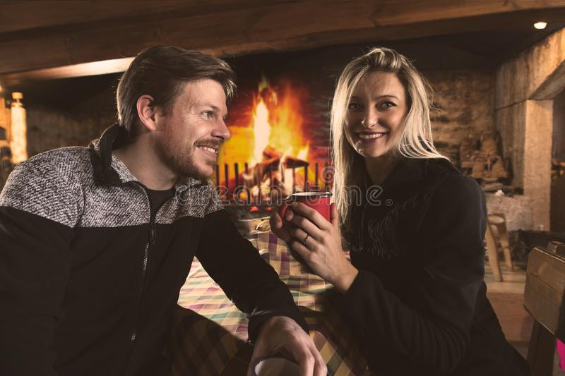 Man and woman drinking tea in cozy place. Handsome men and beautiful women in warm sweaters drinking hot tea from metal mugs, sitting in cozy place of a royalty free stock images