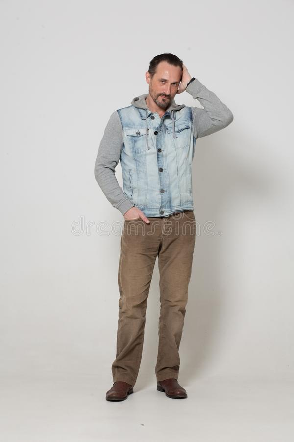 Portrait of fashion dressed man. Handsome men in brown jeans standing on white background stock image