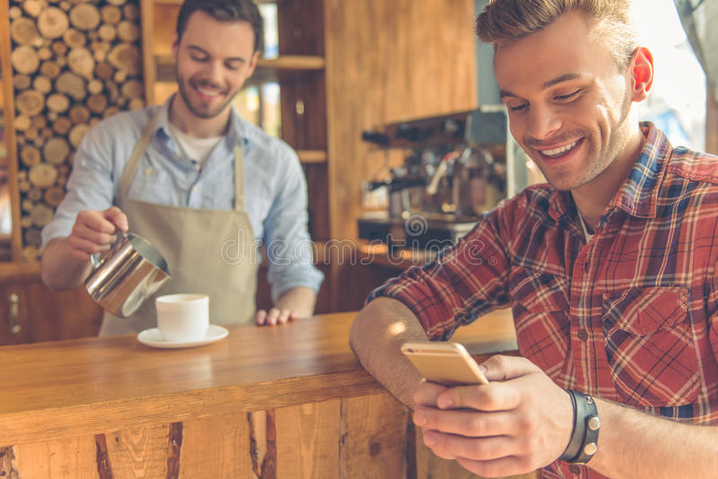 Handsome men at cafe. Handsome young men is using a smartphone and smiling, in the background barista adding milk to coffee, standing at the bar counter stock photography