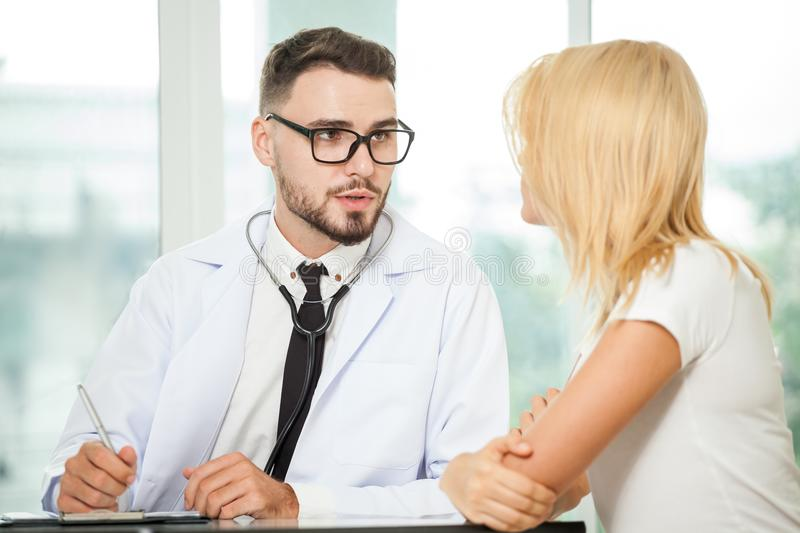 Handsome man doctor talking with young woman patient and making royalty free stock photo