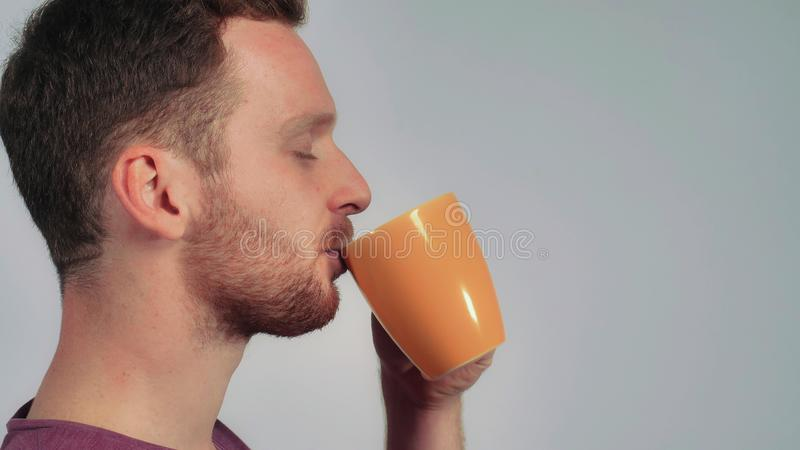 Handsome men relish mug with tea. Close up portrait caucasian man with red hair drinking coffee. student holding orange cup with drink stock photo