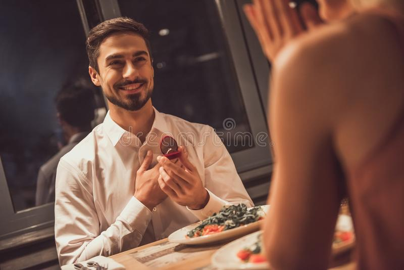 Man proposing in restaurant. Handsome men is smiling while holding an engagement ring and proposing to his girlfriend in a restaurant stock image