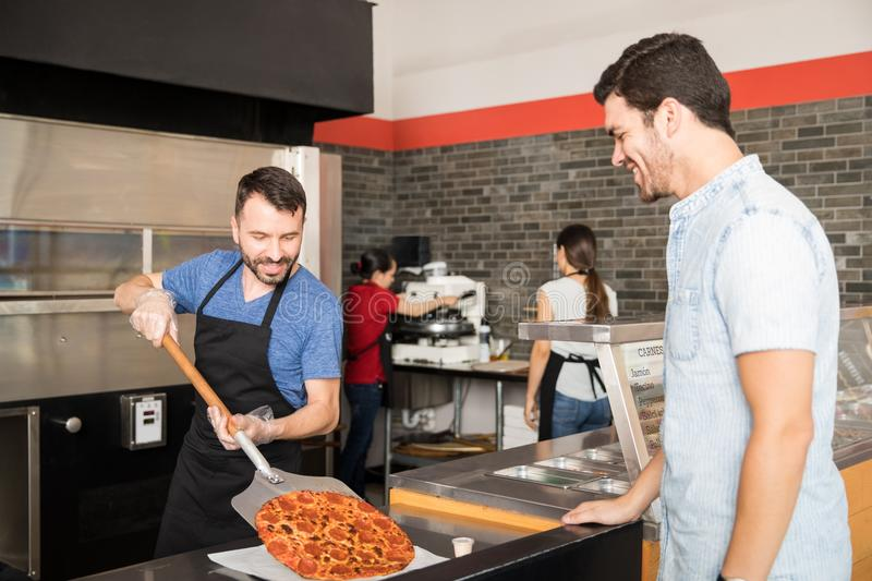 Smiling chef putting pizza on plate using shovel while customer stock photos