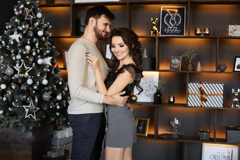 Beautiful couple of young lovers in Christmas interior. Handsome man in sweater hugs cheerful brunette model girl in a stock image