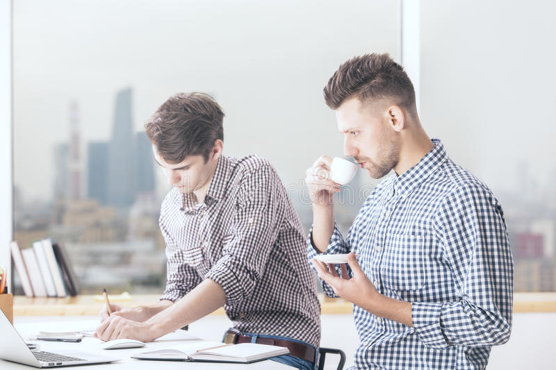 Handsome men working on project. Two handsome caucasian businessmen working on project in modern office stock photos