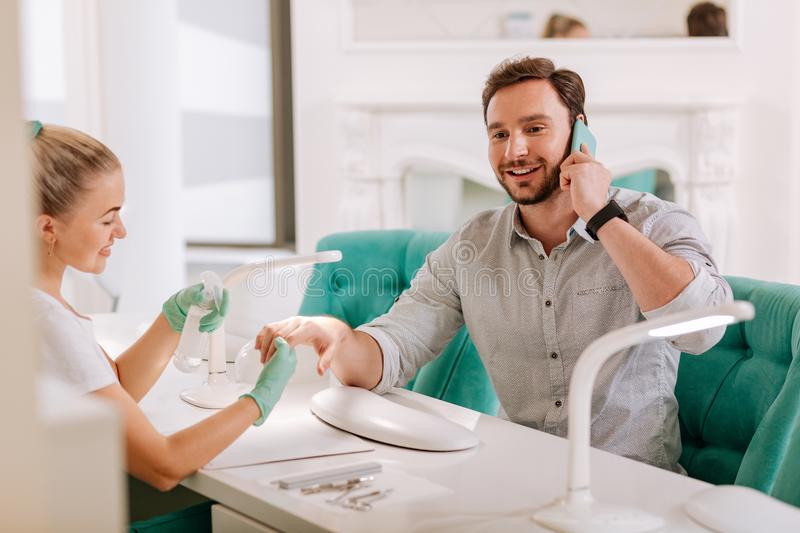 Handsome metrosexual visiting fancy nail salon. Handsome metrosexual. Handsome metrosexual talking on the phone while visiting fancy nail salon royalty free stock photos