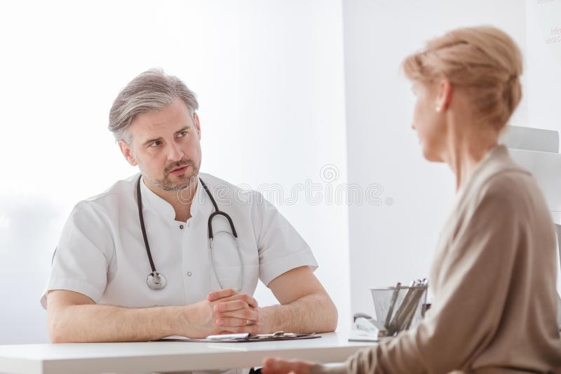 Handsome middle age doctor and female patient at hospital office royalty free stock photo