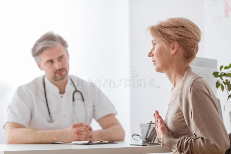 Handsome middle age doctor and female patient at hospital office. Handsome middle age doctor and patient at hospital office royalty free stock images