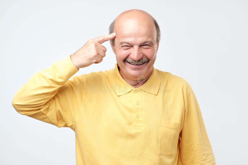 Senior man smiling pointing to head with one finger, great idea or thought. Handsome middle age hoary senior man smiling pointing to head with one finger, great royalty free stock photography