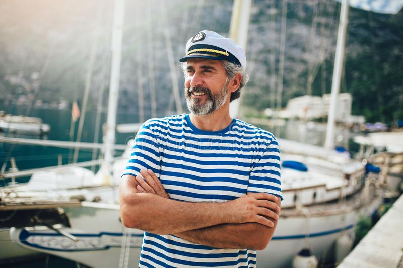 Middle age man in marina with a happy face standing and smiling with a confident stock image