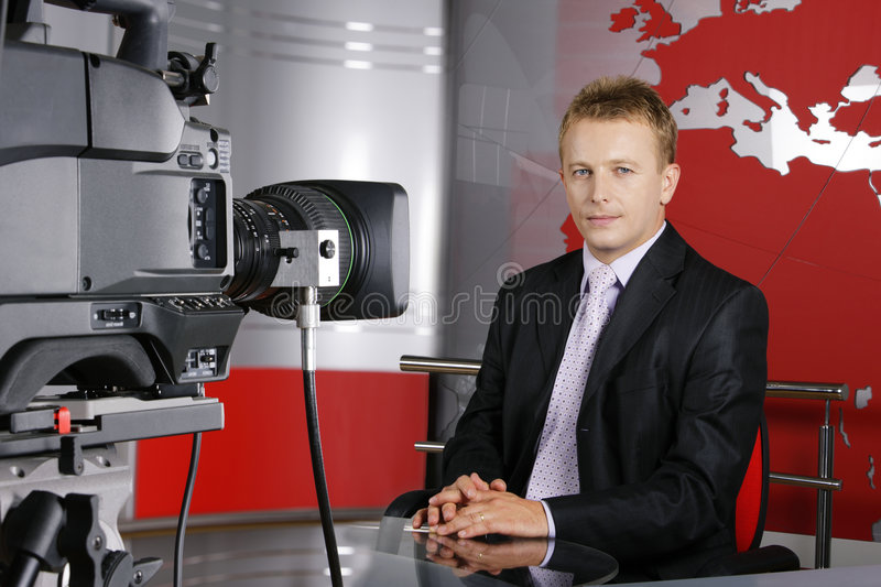 Handsome middle age television news presenter. Blond middle age news presenter in studio in front of the video camera stock image
