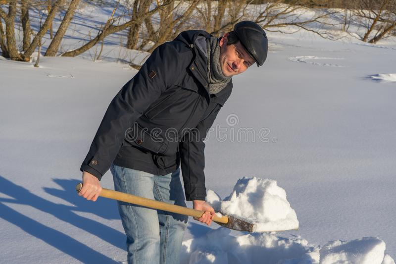 Handsome middle-aged caucasian man cleaning snow on household plot in sunny day. Man with shovel paving path from country house to. Road. Winter active leisure royalty free stock images