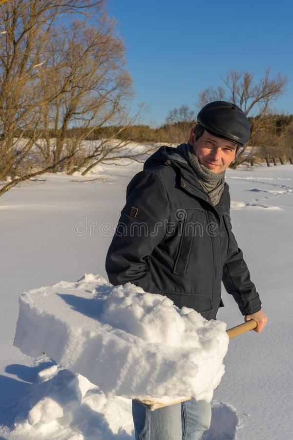 Handsome middle-aged caucasian man cleaning snow on household plot in sunny day. Man with shovel paving path from country house to. Road. Winter active leisure royalty free stock image