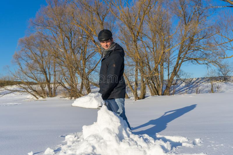 Handsome middle-aged caucasian man cleaning snow on household plot in sunny day. Man with shovel paving path from country house to. Road. Winter active leisure stock images
