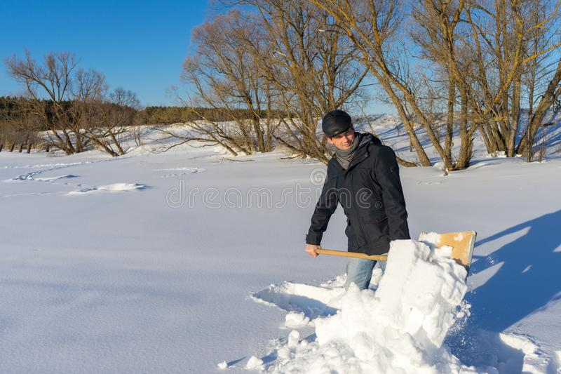 Handsome middle-aged caucasian man cleaning snow on household plot in sunny day. Man with shovel paving path from country house to. Road. Winter active leisure stock photography