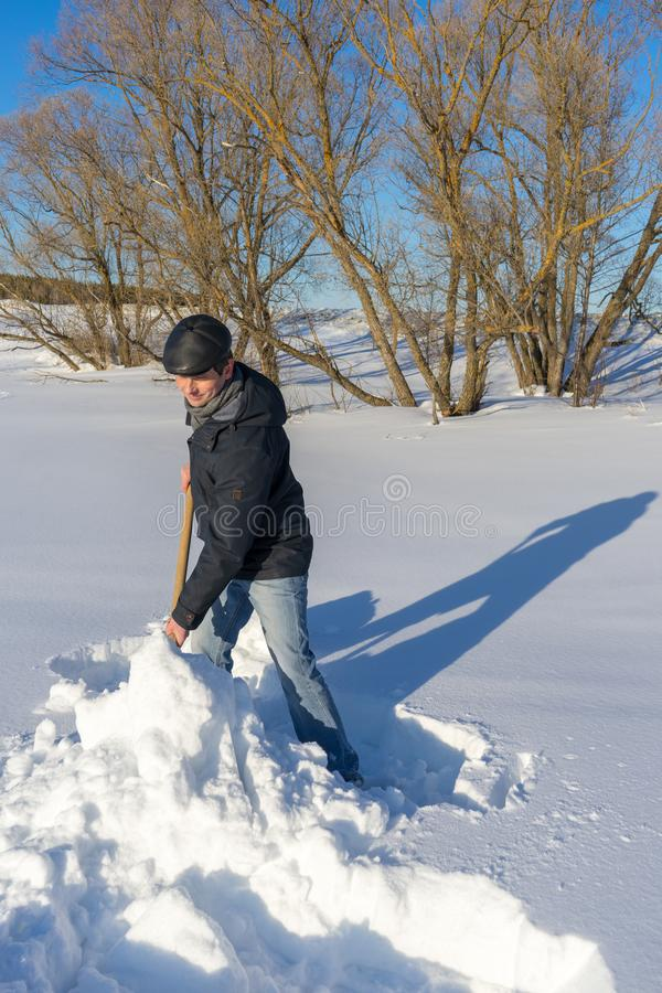 Handsome middle-aged caucasian man cleaning snow on household plot in sunny day. Man with shovel paving path from country house to. Road. Winter active leisure stock image