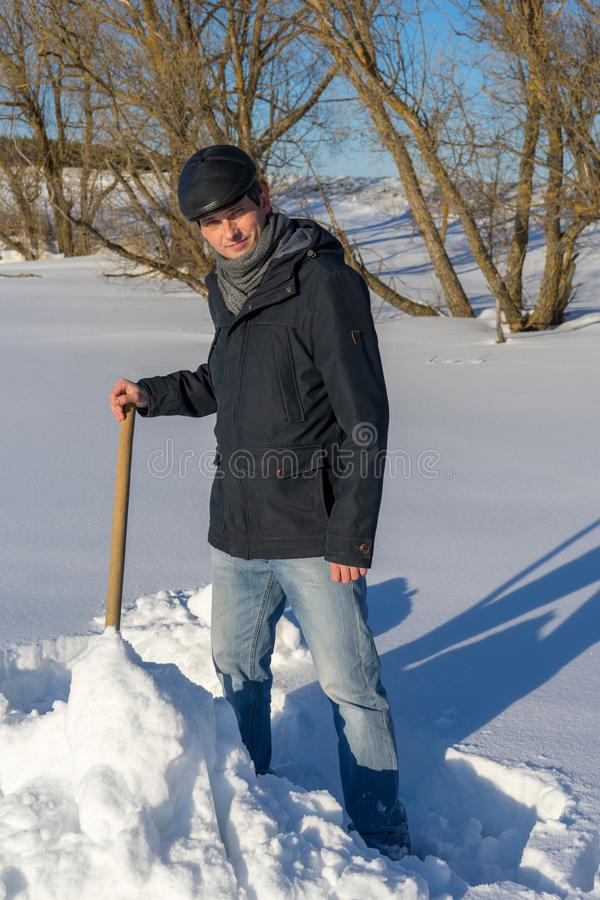 Handsome middle-aged caucasian man cleans snow on household plot. In sunny day. Man with shovel paving path from country house to road. Winter active leisure stock photo