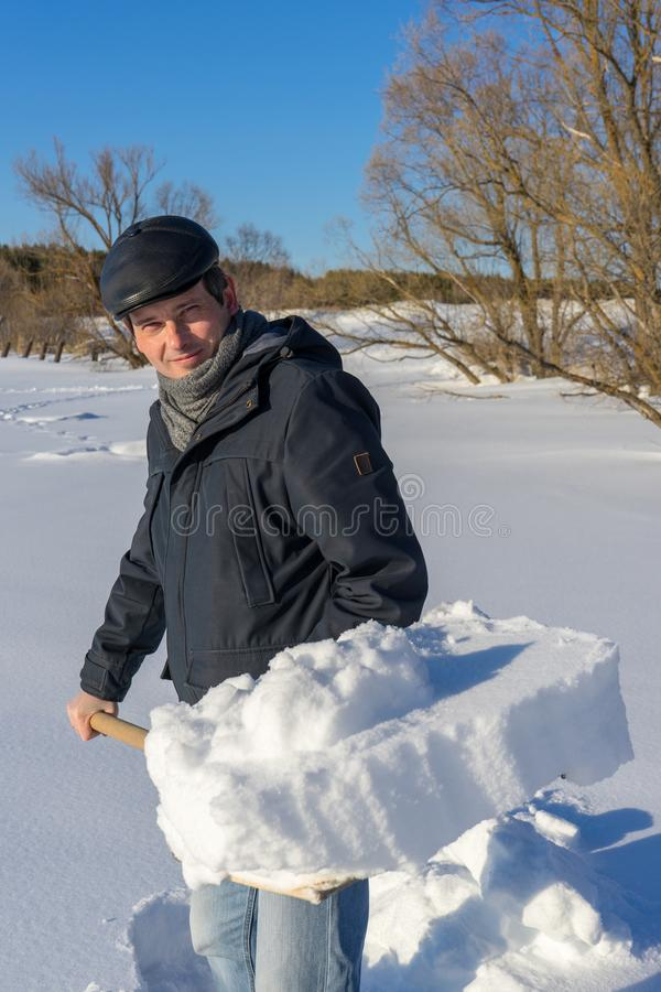 Handsome middle-aged caucasian man cleans snow on household plot. In sunny day. Man with shovel paving path from country house to road. Winter active leisure royalty free stock images