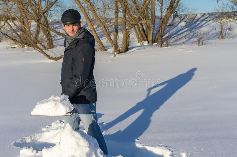 Handsome middle-aged caucasian man cleans snow on household plot. In sunny day. Man with shovel paving path from country house to road. Winter active leisure royalty free stock photos