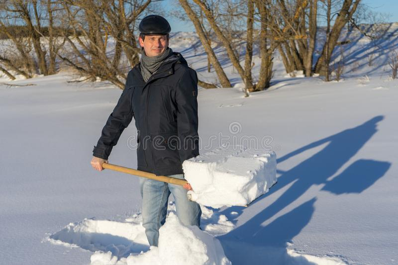 Handsome middle-aged caucasian man cleans snow on household plot. In sunny day. Man with shovel paving path from country house to road. Winter active leisure stock images