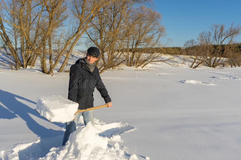 Handsome middle-aged caucasian man cleans snow on household plot. In sunny day. Man with shovel paving path from country house to road. Winter active leisure stock photography