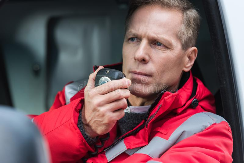 Handsome middle aged male paramedic talking by portable radio while sitting. In ambulance stock image