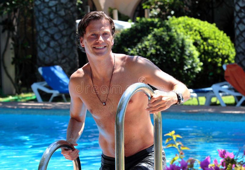 Handsome middle aged man climbing out of swimming pool stock images