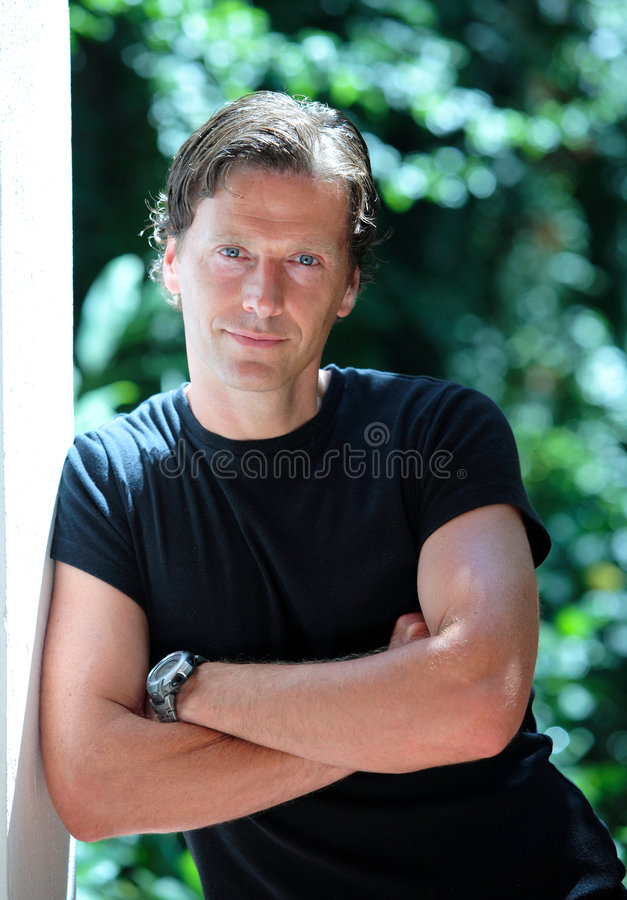 Handsome middle aged man leaning against wall in the sun royalty free stock photos