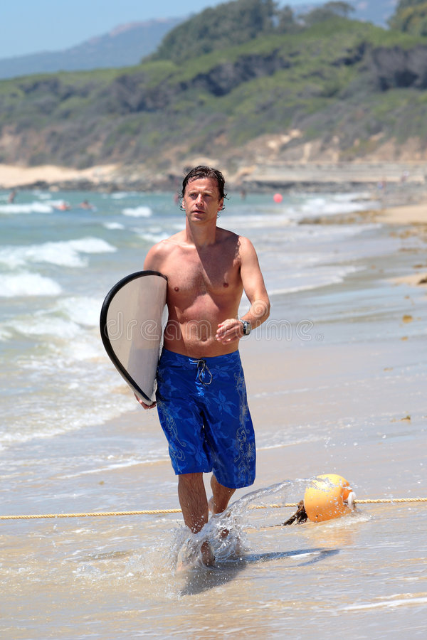 Handsome middle aged man waliking along beach stock photography