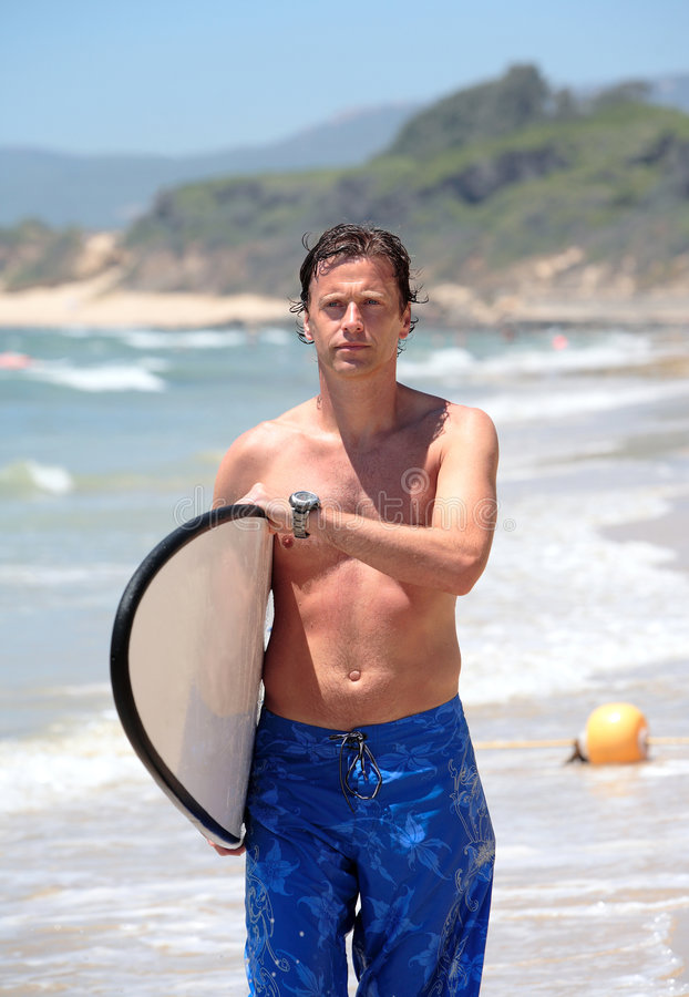 Handsome middle aged man waliking along beach royalty free stock image