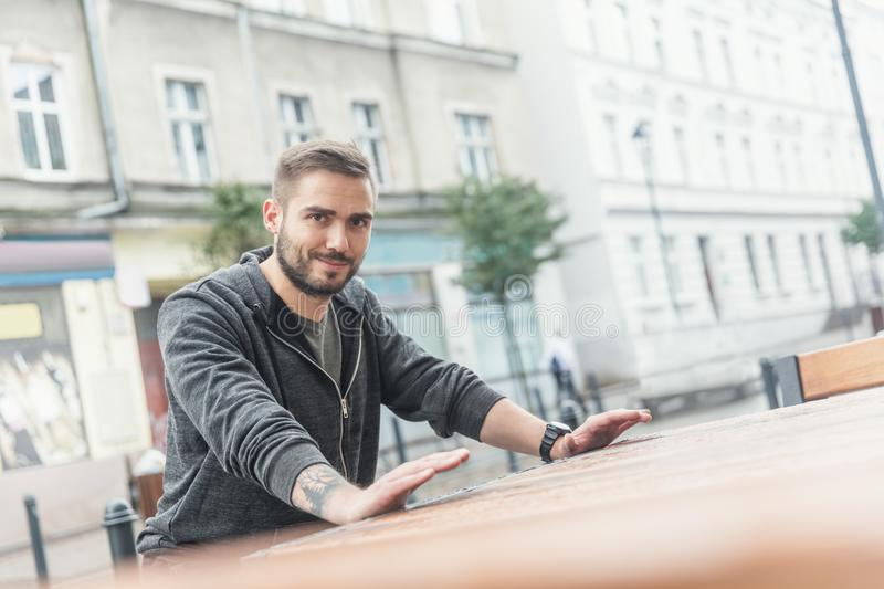 Handsome millenial man in a cityscape. stock image