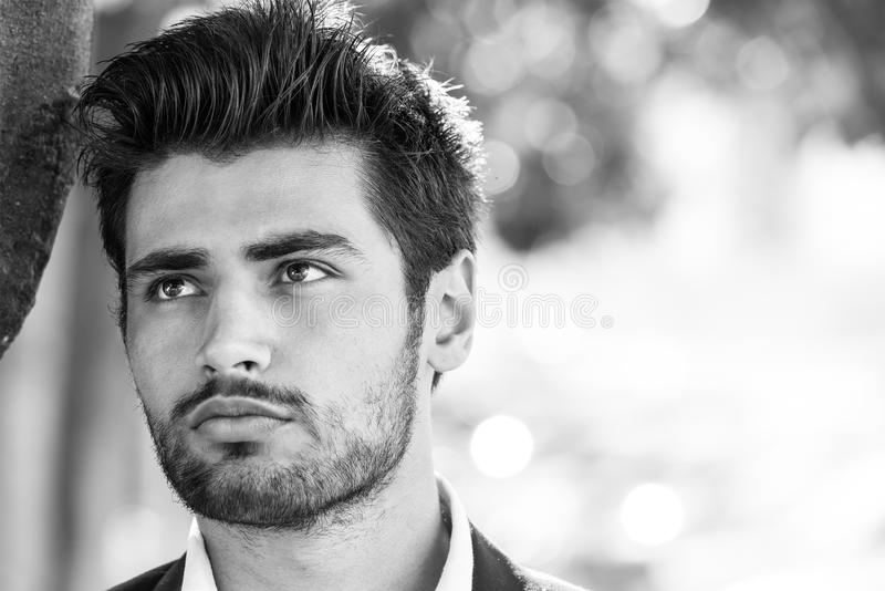 Handsome model man portrait. Hope. Black and white. Portrait of a charming and beautiful young man. Blacks hair and perfect face. White shirt. Outdoor. Beauty stock images