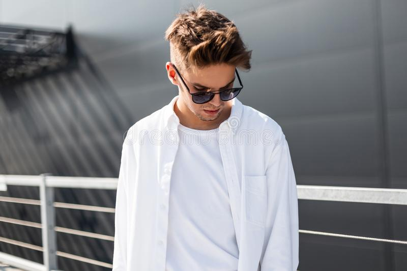 Handsome modern young man in fashionable white clothes in stylish black sunglasses with trendy hairstyle stands on a bright sunny. Day near a gray building in royalty free stock photography