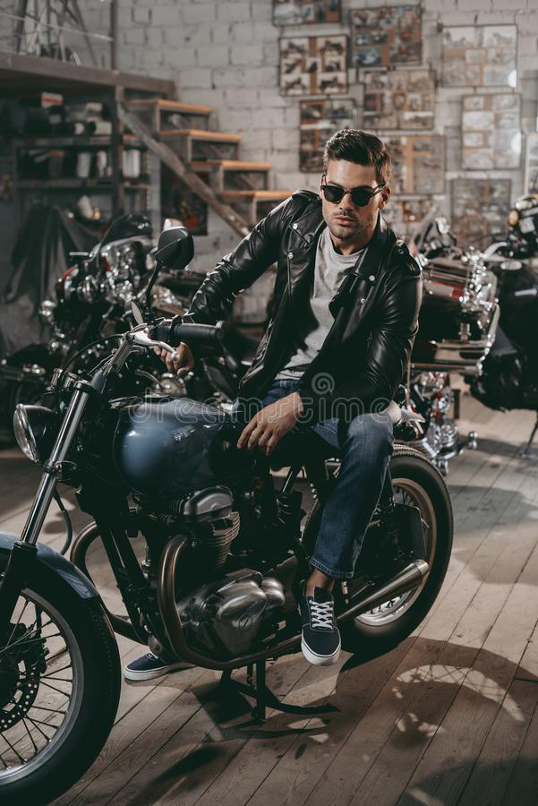 handsome motorcyclist in sunglasses and black leather jacket with classic motorbike royalty free stock photography