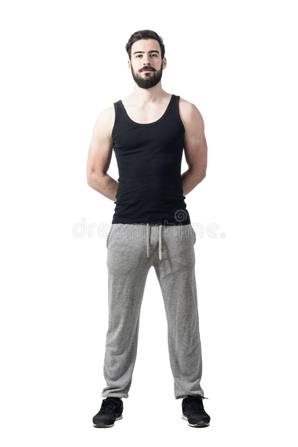 Handsome muscular athlete with hands behind back looking at camera royalty free stock photo