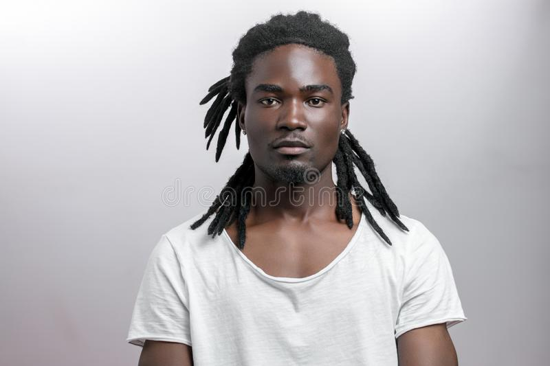 Muscular black man looking camera on white backgound stock image