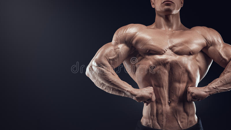 Handsome muscular bodybuilder posing on Front Lat Spread. Display lat width from the front, chest thickness, shoulder width, front arm and forearm size stock images