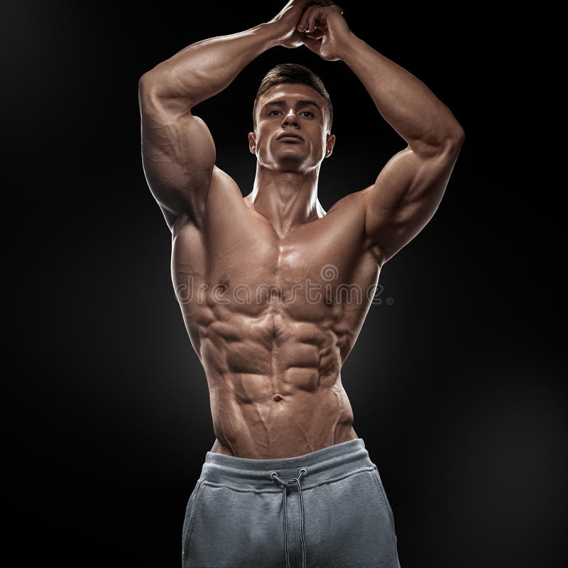 Handsome muscular bodybuilder posing on Front Lat Spread. Display lat width from the front, chest thickness, shoulder width, front arm and forearm size royalty free stock photo