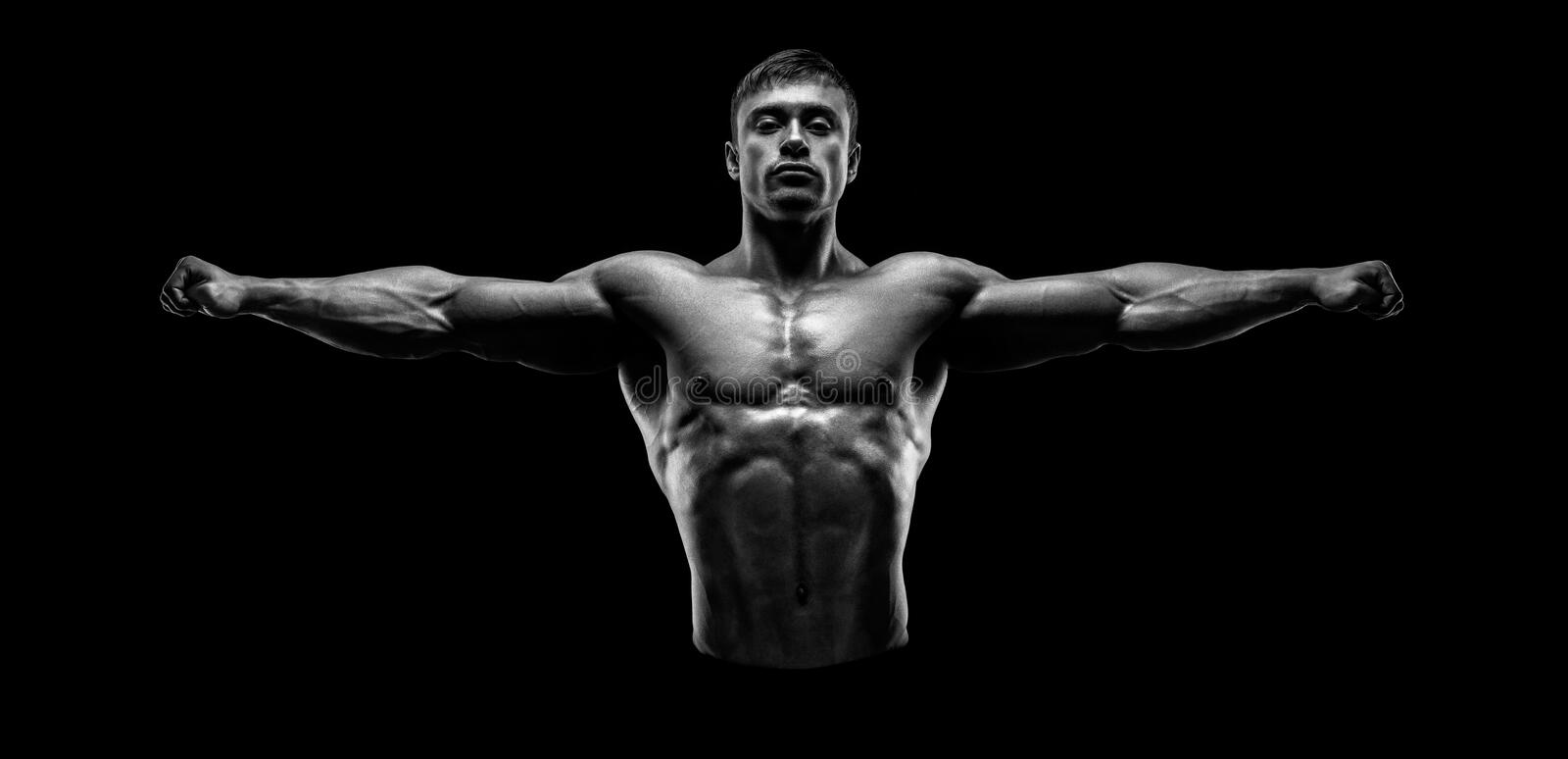 Handsome muscular bodybuilder posing and keeping arms outstretch stock images