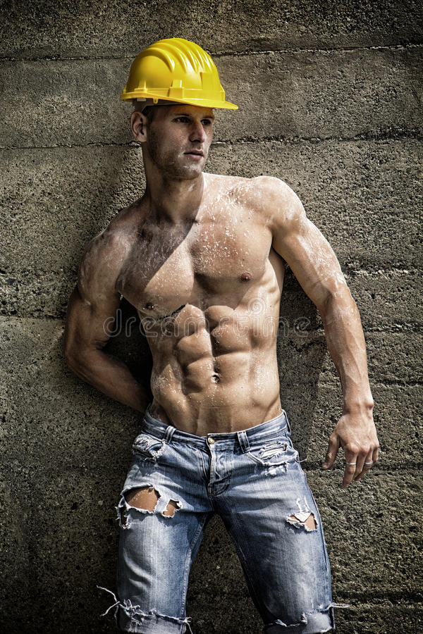 Handsome muscular construction worker standing stock photos