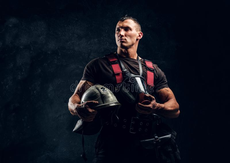 Handsome muscular fireman holding a helmet and oxygen mask standing in the studio against a dark textured wall stock photos