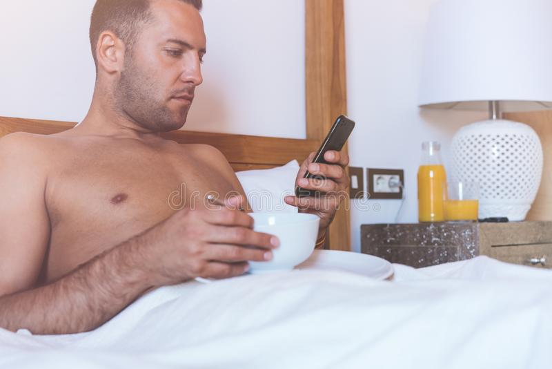 Handsome muscular male gay lying on bed with smartphone and cup of black coffee.Healthy breakfast in the morning at royalty free stock photo